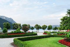 View of the mountains, the lake and the embankment of the city with trimmed trees, shrubs, lawn and flower beds.  royalty free stock photos