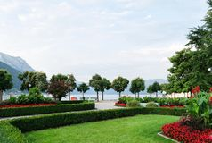 View of the mountains, the lake and the embankment of the city with trimmed trees, shrubs, lawn and flower beds stock photo