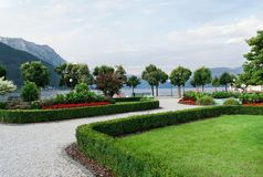 View of the mountains, the lake and the embankment of the city with trimmed trees, shrubs, lawn and flower beds stock photography