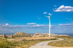 View of a mountains landscape with road and wind turbine on top. In Portugal, environment, electricity, mill, technology, environmental, nature, windmill stock photography