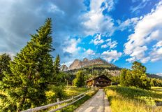 View of the mountains of the Rosengarten group Rosengarten with meadows and fir trees, a road and a mountain hut under a blue cl royalty free stock photography