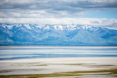 Bridger Bay near Antelope Island State Park in Utah, with snow capped mountains. View of mountains and salt flats from Antelope Island State Park in Utah stock image