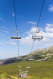 View on mountains in summer with ski lift on blue sky background Royalty Free Stock Images