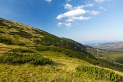 View on mountains in summer with ski lift on blue sky background Stock Photo