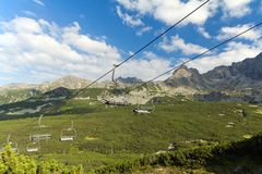 View on mountains in summer with ski lift on blue sky background Royalty Free Stock Photography