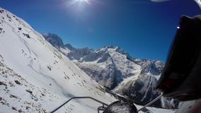 View of mountains, sun and blue sky from the chair lift. First person view stock video footage