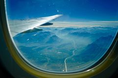 View of mountains and valley from airplane window stock images