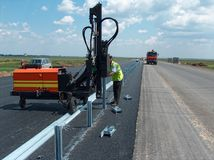 Road worker mounting guardrail. View of mounting the roadside guardrail Royalty Free Stock Images