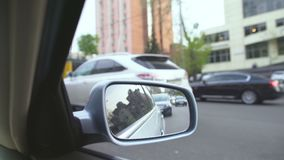 View from moving automobile, reflection in rearview mirror. Traffic jam in city stock video