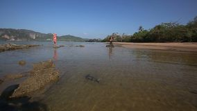 View of moving camera along water towards models under low tide stock video