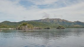 View from a moving ferry. The Busanga Mountains. Tropical landscape of the Palawan Islands. A lonely boat in the. Distance. The city of Coron. Philippines stock video