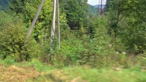 View from a moving train. Train passes by road and a mountain river among wooded hills stock video