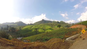 View from moving vehicle of tea plantations in the foothills on the roads of Sri Lanka. stock video footage