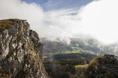 View from Mt Dore mountain peak in Eastern France. View to the valley floor with clouds, sky and sunlit rock face to the foreground Stock Image