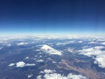 View of Mt. Fuji with clear blue sky and clouds, outside the plane window when heading to Hong Kong, Haneda Airport, Japan royalty free stock photography