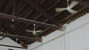 View on multiple ceiling fans blowing air. Three symmetrical and identical ceiling fans or ventilators attached to roof of huge industrial open space move air stock footage
