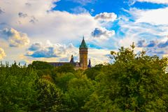 View of Musée de la Banque in Luxembourg City, Luxembourg, with green trees at the foreground and a beautiful sky with clouds and stock images