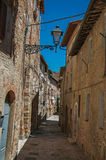 View of narrow alley with old buildings and lamps in Colle di Val d`Elsa. A graceful village with its historic center preserved and known by its crystal Royalty Free Stock Image