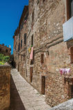 View of narrow alley with old buildings and lamps in Colle di Val d`Elsa. A graceful village with its historic center preserved and known by its crystal Royalty Free Stock Photos