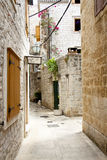 View on narrow alley - Trogir, Croatia. Stock Photos
