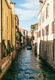 View of a narrow canal in Venice with a boat on a side. Stock Photo