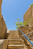 View of a narrow stone street through a staircase in the old city of Jaffa, with the old houses still. View of a narrow stone street through a staircase in the royalty free stock images