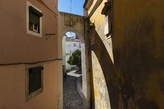 View of a narrow street with an arch and traditional old buildings in the historic neighborhood of Alfama in Lisbon, Portugal. Concept for visit Lisbon Stock Photos