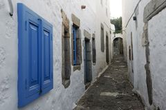 A view of a narrow street with arch and wooden windows and doors with white wall stone architecture of the island Patmos, Greece.  royalty free stock images
