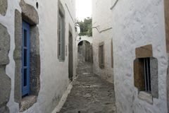A view of a narrow street with arch and wooden windows and doors with white wall stone architecture of the island Patmos, Greece.  royalty free stock image