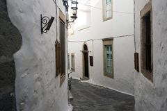 A view of a narrow street with arch and wooden windows and doors with white wall stone architecture of the island Patmos, Greece.  royalty free stock photo