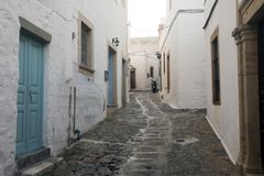 A view of a narrow street with arch and wooden windows and doors with white wall stone architecture of the island Patmos, Greece.  royalty free stock photos