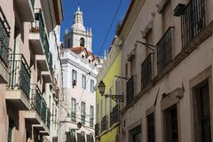 View of a narrow street and buildings with a tower of the Sao Vincente de Fora church on the backrgound, in the historic neighbour. Hood of Alfama in Lisbon Royalty Free Stock Photo