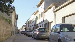 View of narrow street with cars and old houses. Art. Parking space is filled with cars on narrow road under houses on stock video