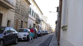 View of narrow streets of european city in summer. Art. Woman walks with dog on narrow street with parked row of cars on. Summer vacation stock footage