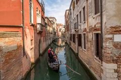View of narrow Venice canal and gondolier. Venetian gondolier punting gondola through green canal waters of Venice Italy stock photography