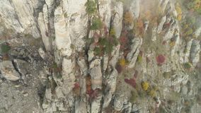 View near rock from ground. Shot. Top view of rock relief near beginning. Autumn colorful bushes and plants at cliff of. Rock stock video footage
