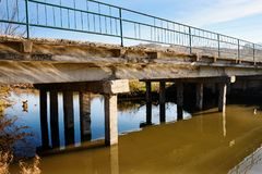 View of the neglected old bridge that consists of concrete slabs. Somewhere in the village. Bridge over the river with muddy water Stock Image