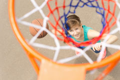 View through the net of a basketball shooter. View from the top through the net of a smiling young teenage female basketball shooter taking aim to throw the ball royalty free stock photography