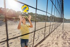 View through the net of boy playing volleyball. View through the net of teenage boy serving the ball during beach volleyball game royalty free stock photography
