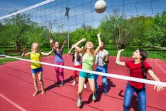 View through net on game of girls playing together Stock Photography