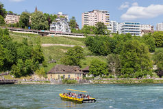 View in Neuhausen am Rheinfall. Neuhausen am Rheinfall, Switzerland - 10 May, 2015: boat on the Rhine river just below the Rhine Falls. The Rhine Falls is the Royalty Free Stock Image