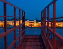 View of Neva and English embankment in St. Petersburg with night illumination through gangway on pier Stock Image