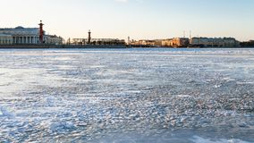 View of Neva river and Spit of Vasilyevsky Island. View of frozen Neva river and Spit of Vasilyevsky Island with Rostral Column and Old Stock Exchange building Royalty Free Stock Image