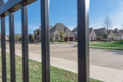 View of nice and comfortable neighborhood through the fence. View of nice, comfortable neighborhood through fence. Nicely trimmed and manicured garden in front Stock Photos