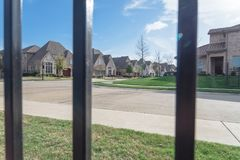 View of nice and comfortable neighborhood through the fence. View of nice, comfortable neighborhood through fence. Nicely trimmed and manicured garden in front Royalty Free Stock Photos