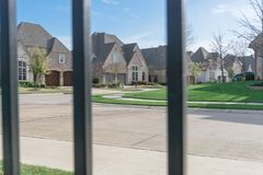 View of nice and comfortable neighborhood through the fence. View of nice, comfortable neighborhood through fence. Nicely trimmed and manicured garden in front Royalty Free Stock Images