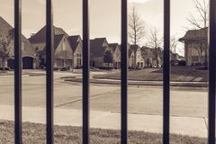 View of nice and comfortable neighborhood through the fence. View of nice, comfortable neighborhood thru fence. Nicely trimmed and manicured garden in front of Stock Image