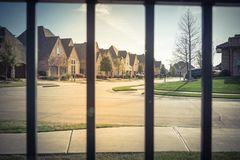 View of nice and comfortable neighborhood through the fence. View of nice, comfortable neighborhood thru fence. Nicely trimmed and manicured garden in front of Royalty Free Stock Photo