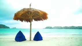 View of nice tropical empty sandy beach with umbrella and beach chair. Good sunny day. Deck chair and beach umbrella on the sand coast stock video