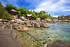 View of nice tropical empty stones beach. With some bungalows in sunny weather. Tao island. Thailand Royalty Free Stock Photography